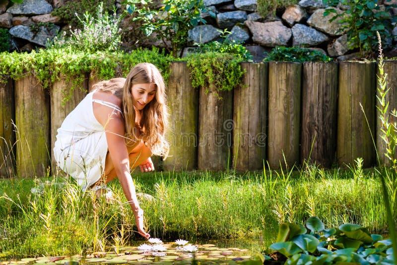Frau, die in Teich in ihrem Garten sitzt lizenzfreie stockfotos