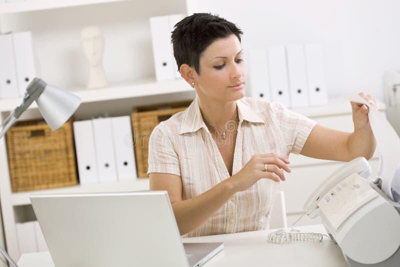 Frau, die Telefaxmaschine verwendet lizenzfreie stockfotos