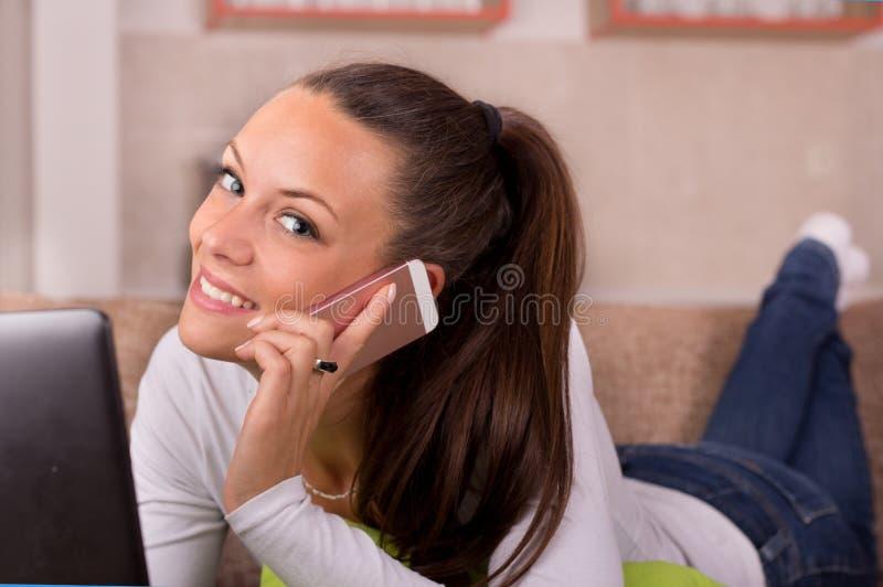 Frau, die am Telefon auf Sofa spricht lizenzfreie stockfotografie