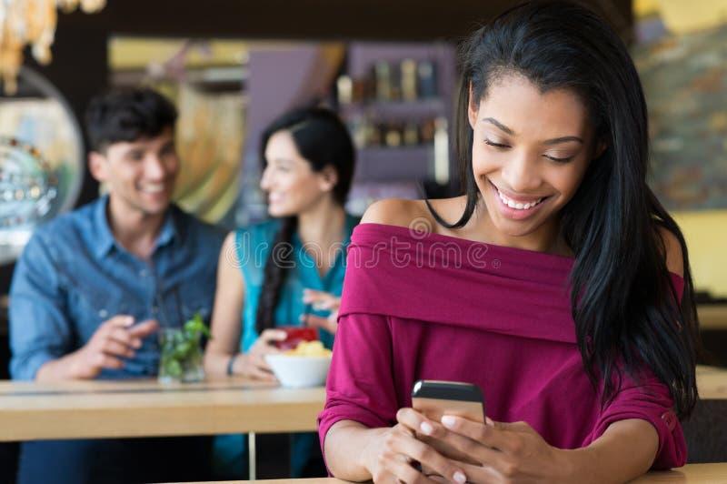 Frau, die am Telefon am Café simst lizenzfreies stockfoto