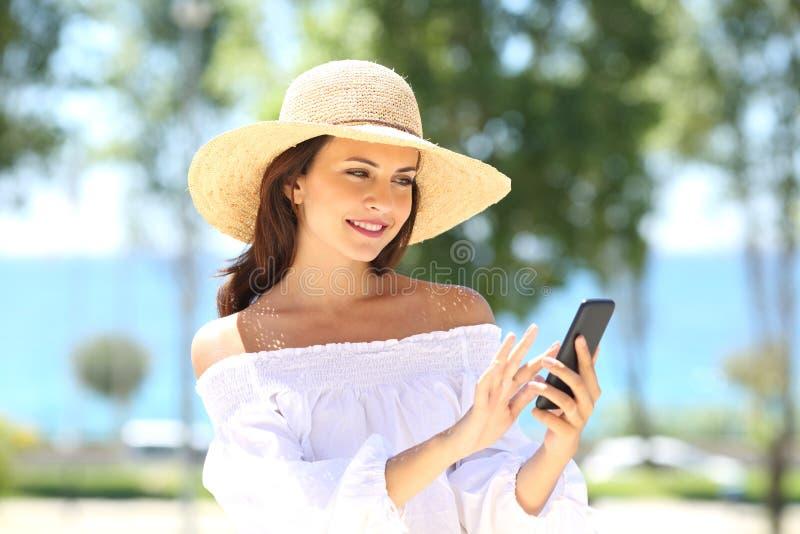 Frau, die am Telefon im Sommer simst lizenzfreies stockbild
