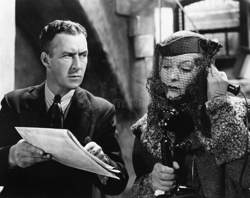 Frau, die am Telefon mit einem Mann zeigt eine Zeitung mit ihr spricht (alle ex Personen dargestellt sind nicht längeres lebendes stockbild