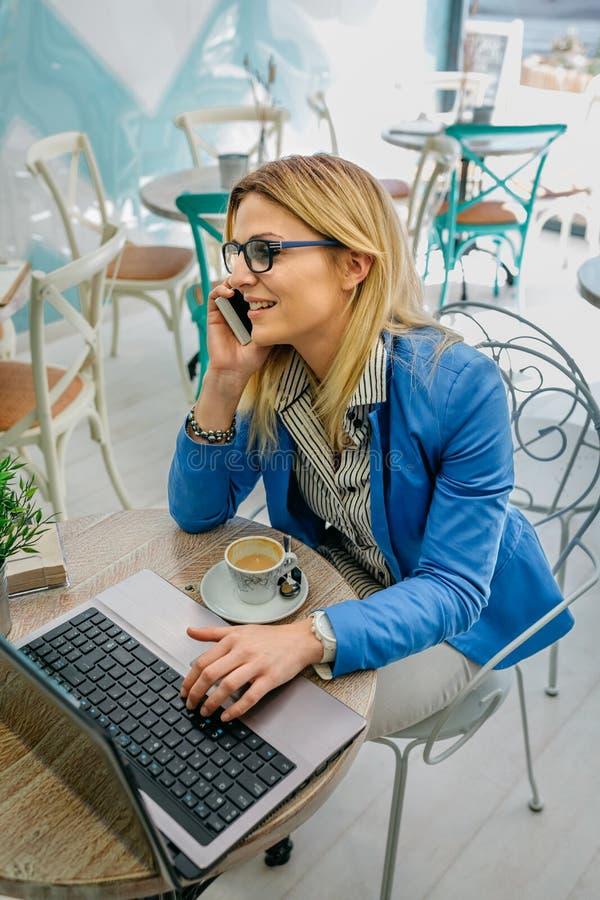 Frau, die am Telefon mit Laptop spricht lizenzfreies stockbild