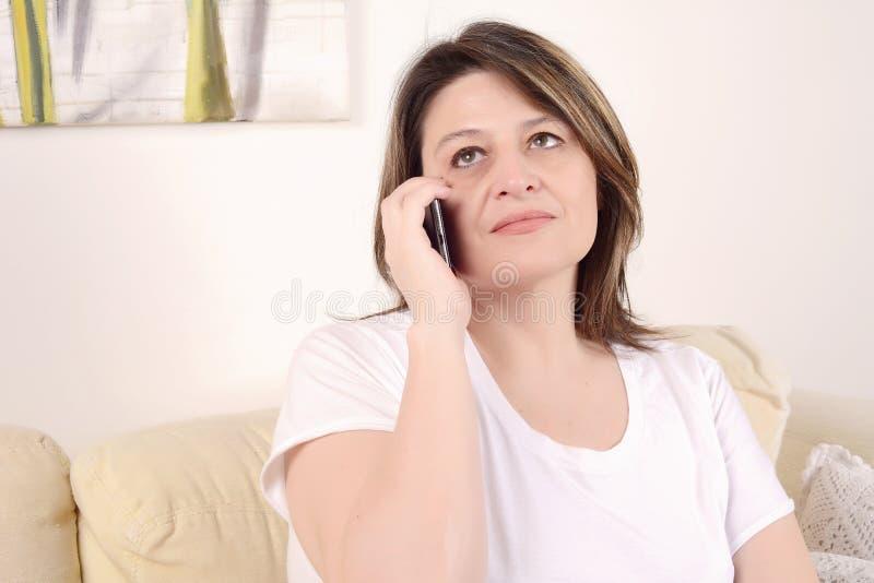 Frau, die am Telefon sitzt auf dem Sofa spricht lizenzfreies stockfoto