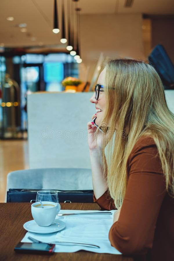 Frau, die am Telefon spricht und im Restaurant lächelt stockfoto