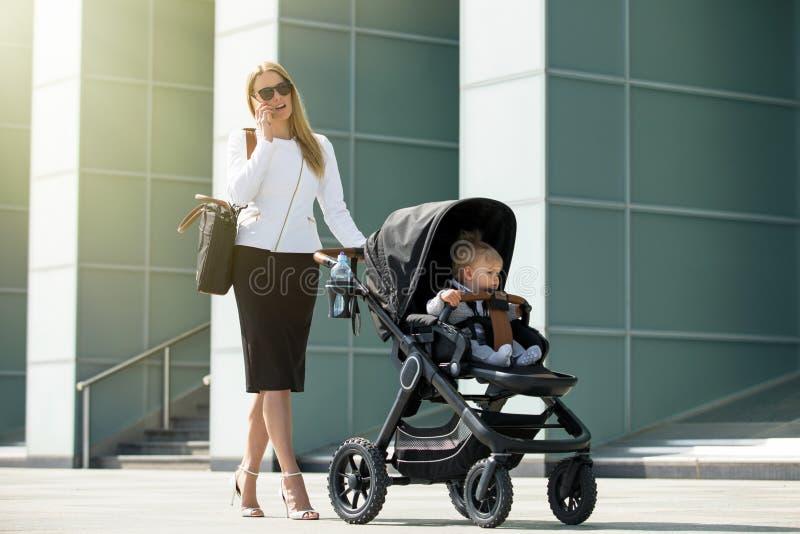 Frau, die am Telefon spricht und Kinderwagen drückt lizenzfreies stockfoto