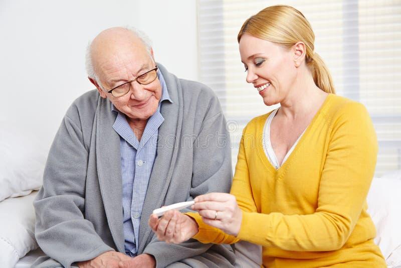 Frau, die Temperatur des Seniors nimmt lizenzfreies stockbild