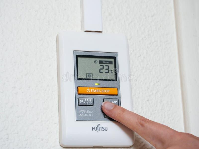 Frau, die Temperatur Klimaanlage wählt lizenzfreies stockbild