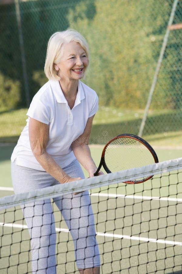 Frau, die Tennis und das Lächeln spielt lizenzfreie stockbilder