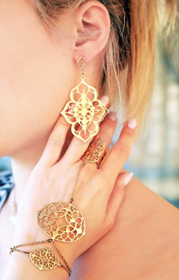 Frau, die teuren Goldschmuck - goldener Armband Ring und earings trägt stockfoto