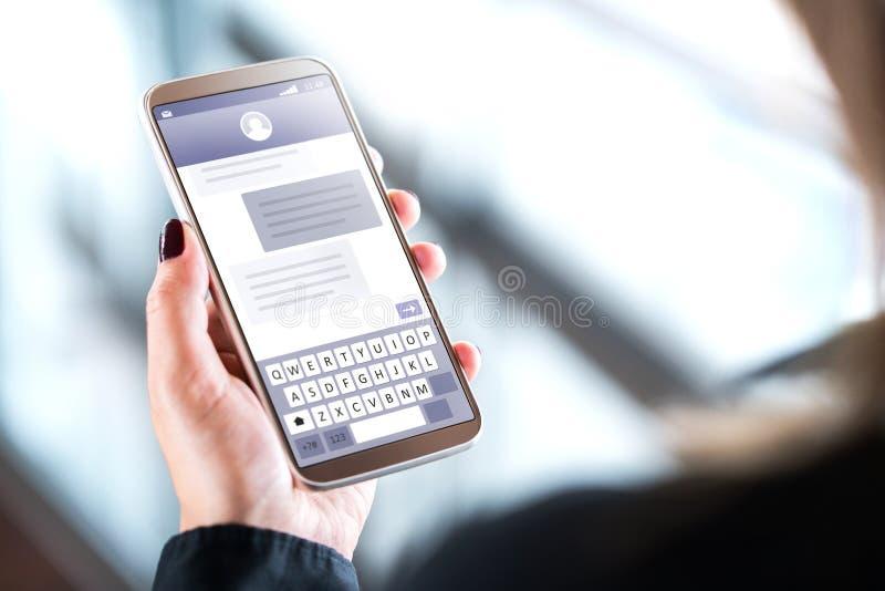 Frau, die Textnachrichten mit Handy sendet stockfotos