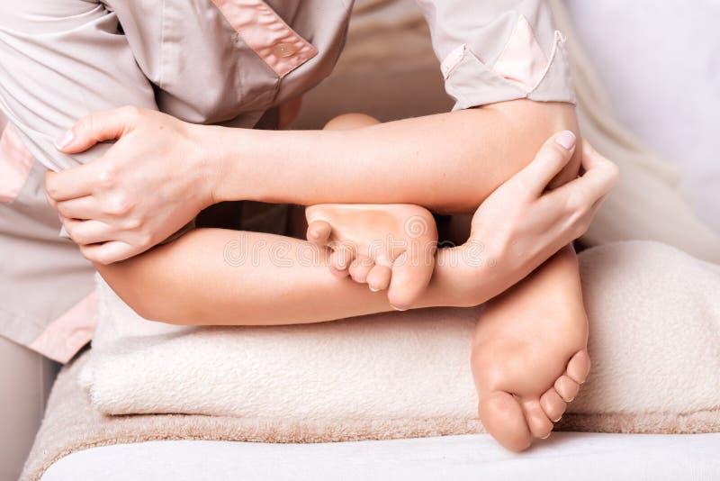 Frau, die therapeutische Fußmassage im Badekurortsalon, Nahaufnahme hat lizenzfreies stockfoto