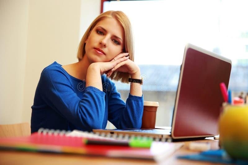 Frau, die am Tisch mit Laptop sitzt lizenzfreies stockbild