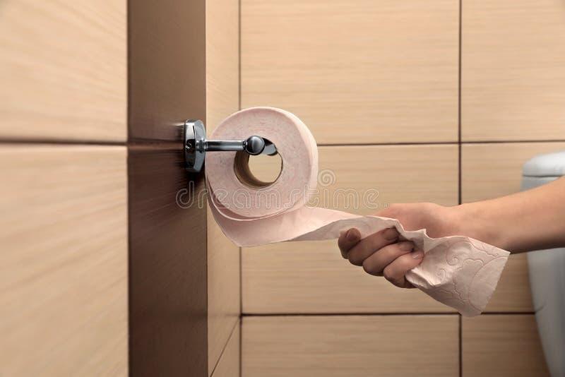 Frau, die Toilettenpapier vom Halter zieht lizenzfreie stockbilder