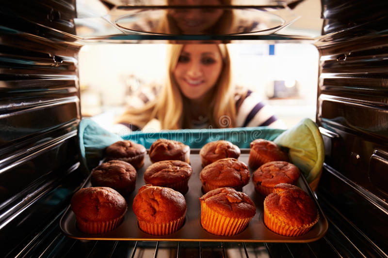 Frau, die Tray Of Baked Muffins Out des Ofens nimmt lizenzfreies stockfoto