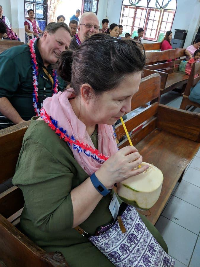 Frau, die in trinkender Kokosmilch der Kirchenbank sitzt stockbild