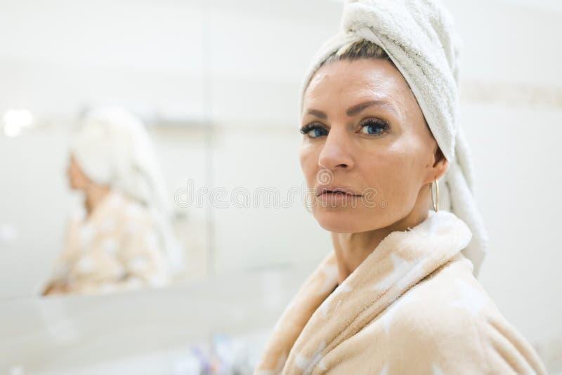 Frau, die Tuch auf Kopf hat, nachdem eine Dusche genommen worden ist Untersuchung Kamera stockbild
