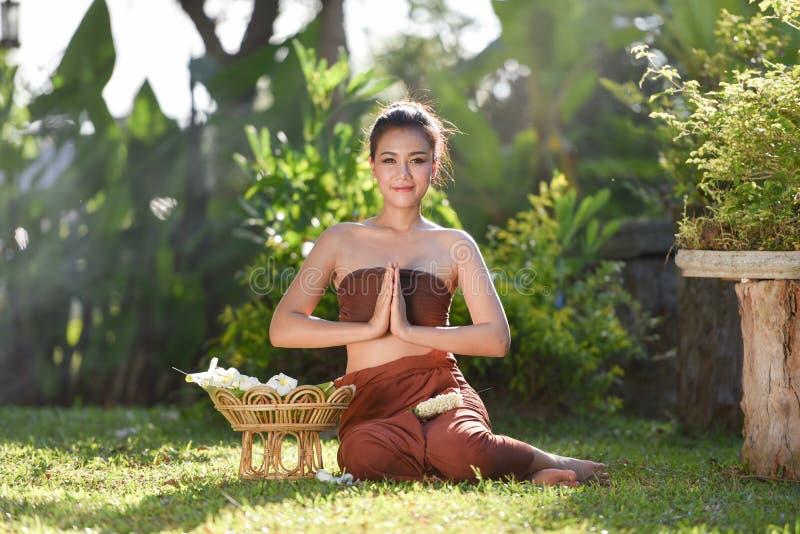 Frau, die typischen thailändischen Kleiderlohnrespekt trägt stockfoto