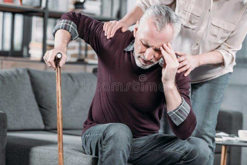 Frau, die um älterem Ehemann mit starken Kopfschmerzen sich kümmert stockfotografie