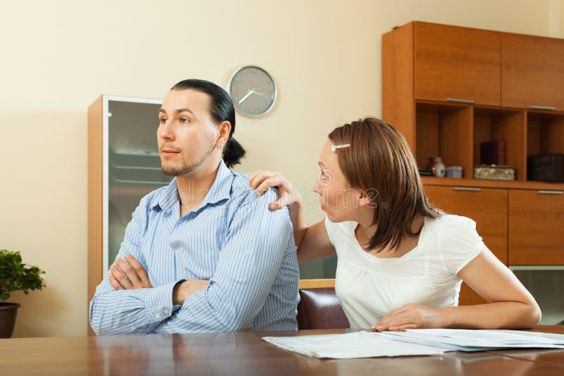 Frau, die um Geld vom Ehemann für den Kauf bittet stockbild