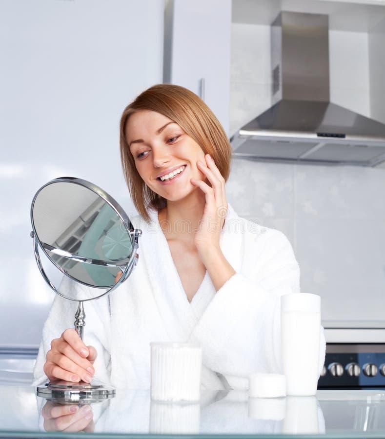 Frau, die um ihrem Gesicht sich kümmert stockfotos