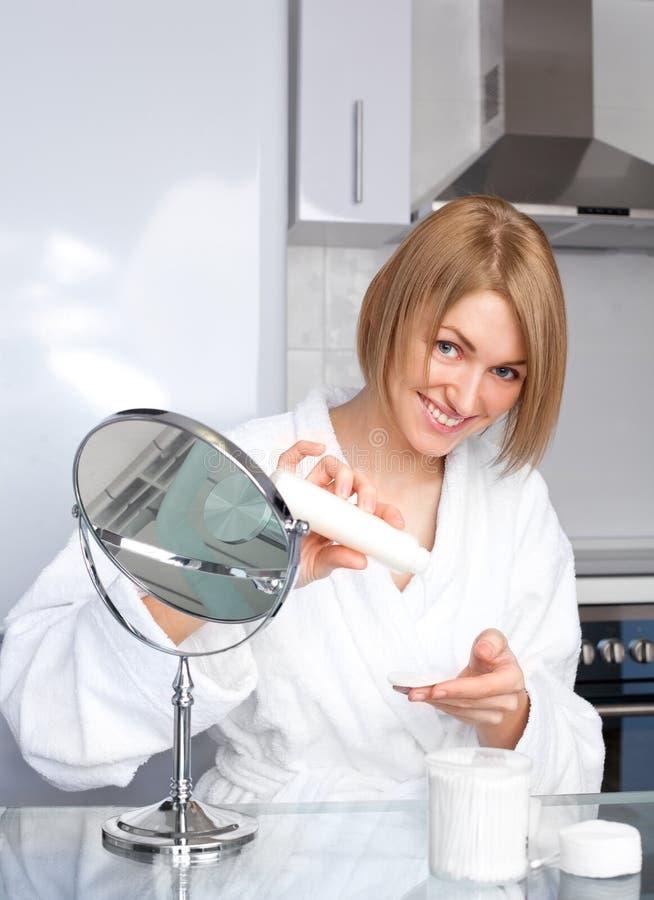 Frau, die um ihrem Gesicht sich kümmert stockfotografie