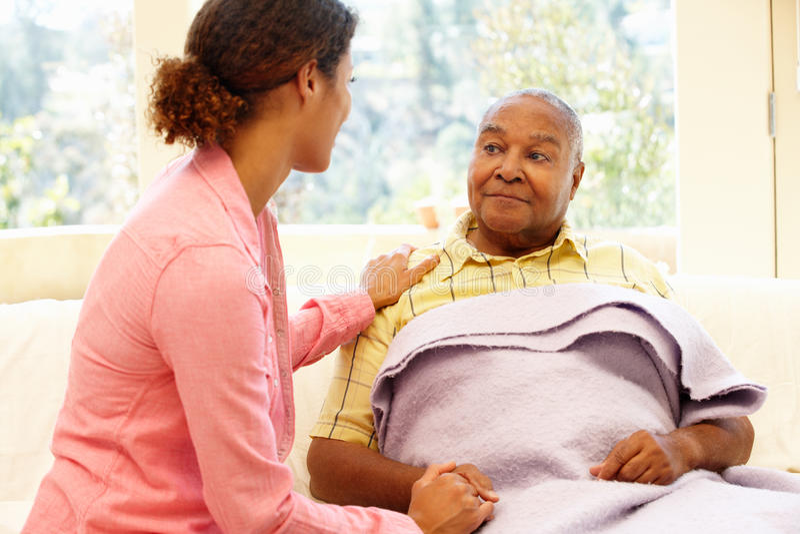 Frau, die um kranken Vater sich kümmert stockfoto