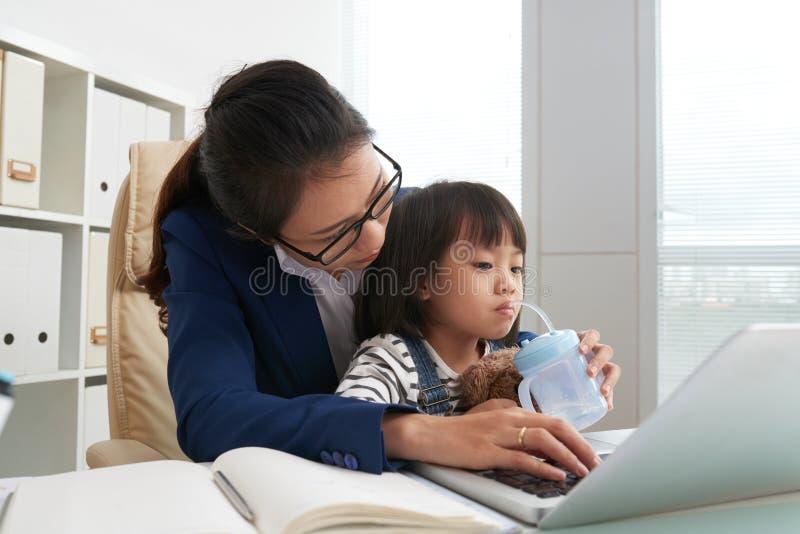 Frau, die um Tochter bei der Arbeit sich kümmert lizenzfreie stockfotos