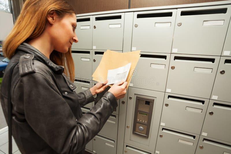 Frau, die Umschläge mit Kopieraum an einer Halle hält lizenzfreies stockfoto
