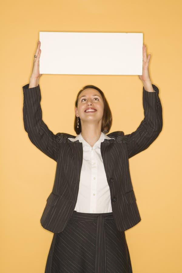 Frau, die unbelegtes Zeichen anhält. stockbilder