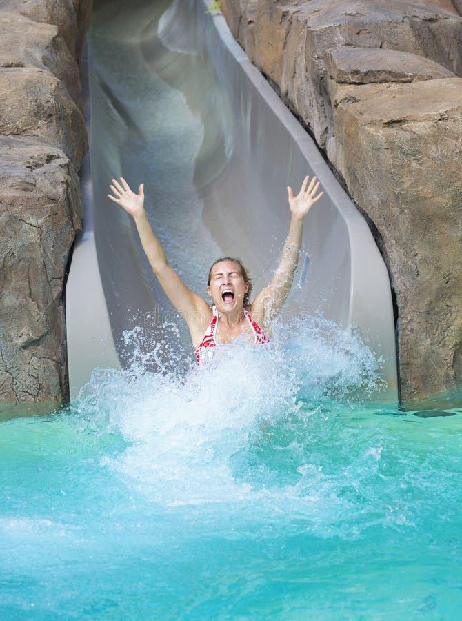Frau, die unten nassen Fahrtwasserrutsche genießt stockfotografie