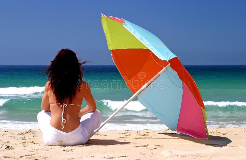 Frau, die unter buntem Sonnenschirm auf weißem sandigem Strand sitzt lizenzfreies stockfoto
