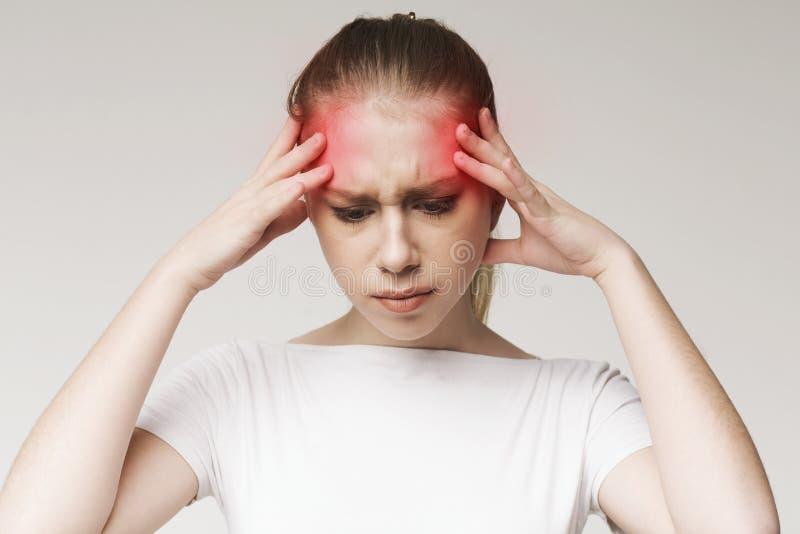 Frau, die unter den Kopfschmerzen, ihre Tempel berührend leidet lizenzfreie stockfotografie