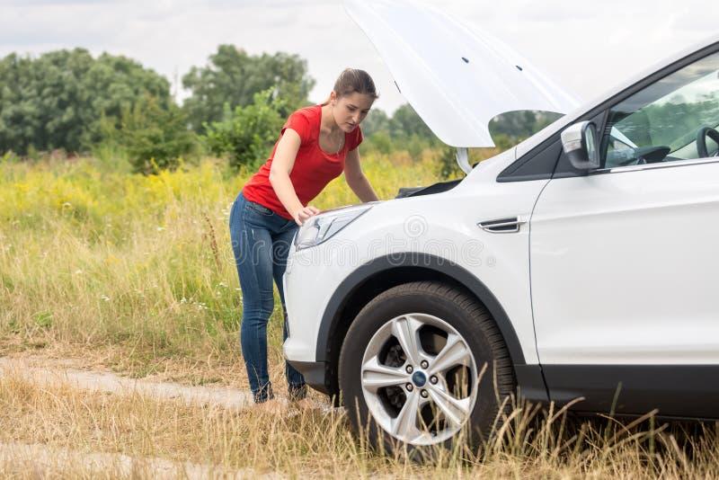Frau, die unter der Haube des überhitzten Autos Wiese betrachtet lizenzfreie stockfotos