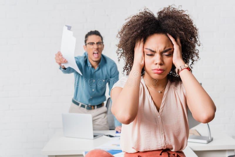 Frau, die unter Druck wegen des verärgerten männlichen Kollegen leidet stockbild