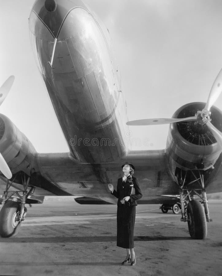 Frau, die unter einem großen Flugzeug oben schaut steht (alle dargestellten Personen sind nicht längeres lebendes und kein Zustan lizenzfreies stockbild