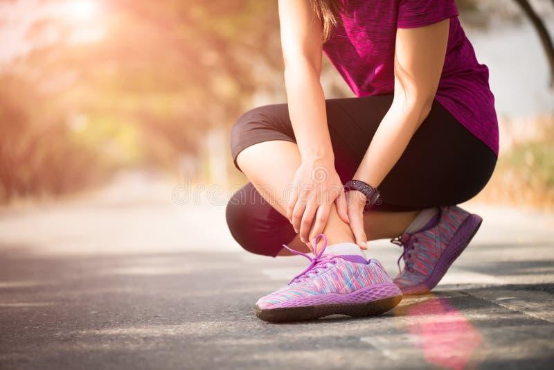 Frau, die unter einer Knöchelverletzung beim Trainieren leidet Laufendes Sportverletzungskonzept stockfoto