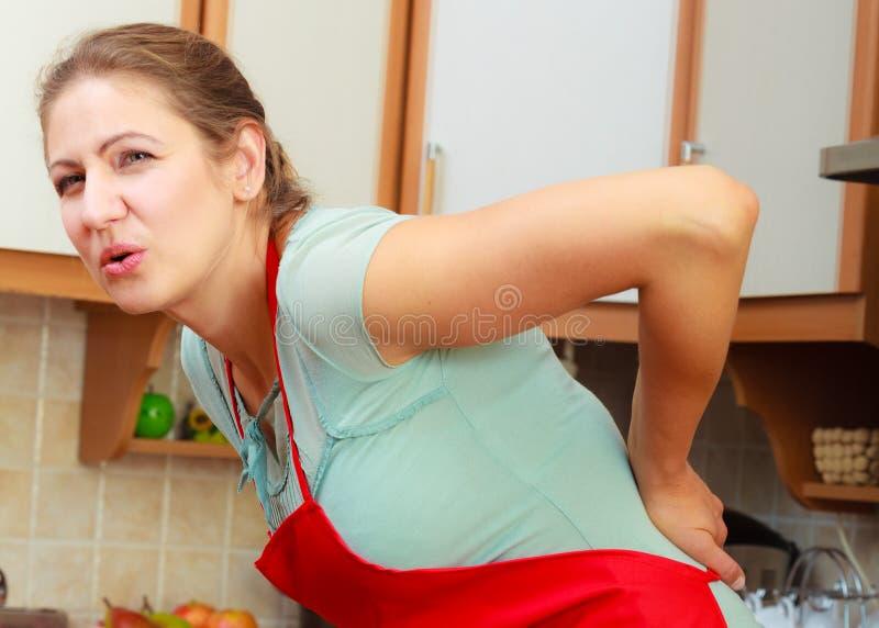 Frau, die unter Rückenschmerzrückenschmerzen leidet lizenzfreie stockfotografie