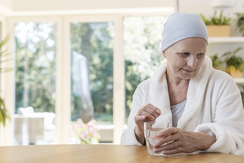 Frau, die unter tragendem Bademantel Eierstockkrebses leiden und Kopftuch, das zu Hause Pillen einnimmt stockbild