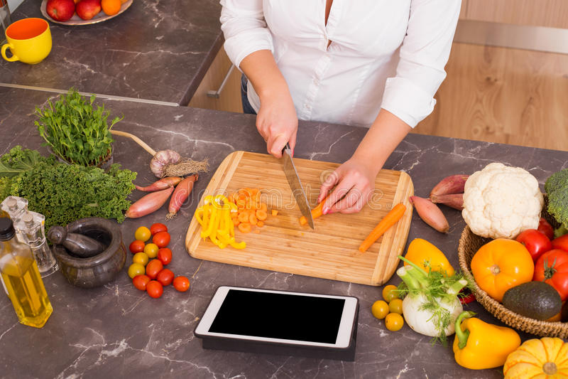 Frau, die unter Verwendung der Tablette schaut und Gemüse schneidet lizenzfreie stockbilder