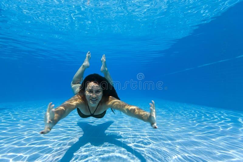 Frau, die unter Wasser in einem Pool schwimmt stockbild