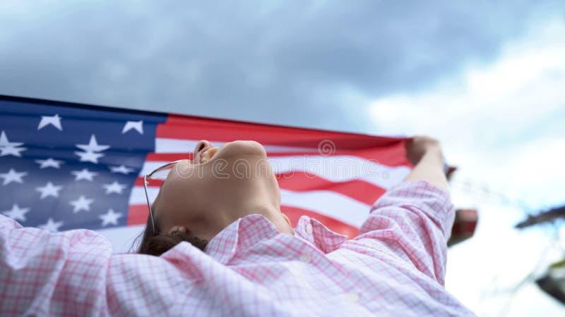 Frau, die US-Flagge, Patrioten, sichere Zukunft für junge Leute in ihrem Land wellenartig bewegt stockbild