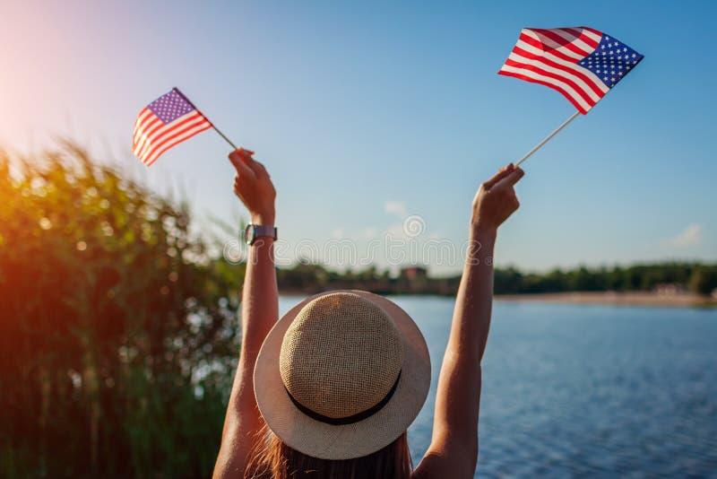 Frau, die USA-Flagge h?lt Feiern des Unabh?ngigkeitstags von Amerika stockfotos