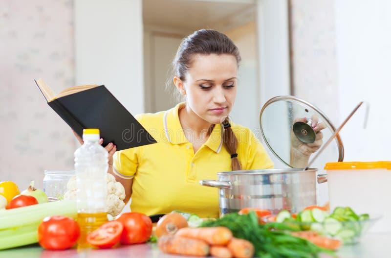 Frau, die Veggielebensmittel mit Kochbuch kocht lizenzfreies stockfoto