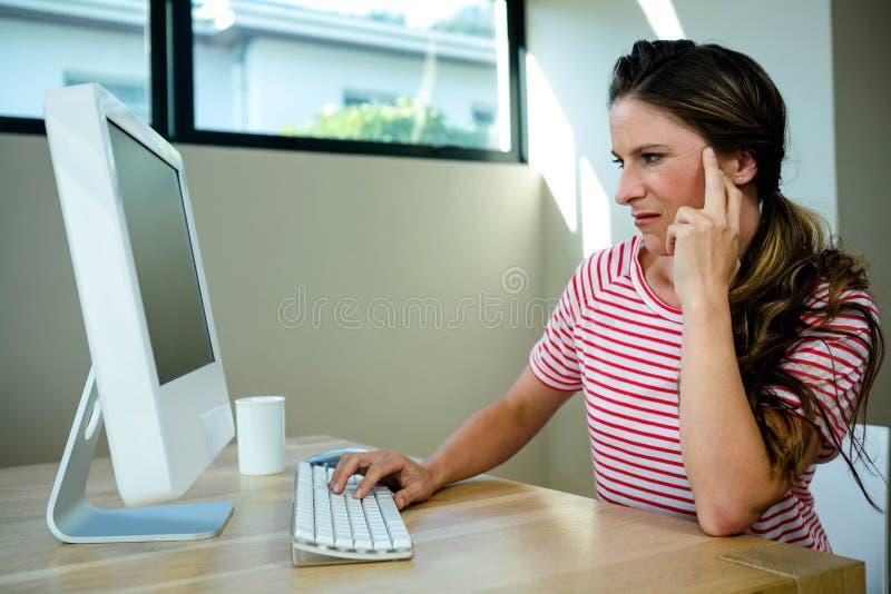 Frau, die verärgertes Sitzen ihrem Computer betrachtet lizenzfreies stockbild