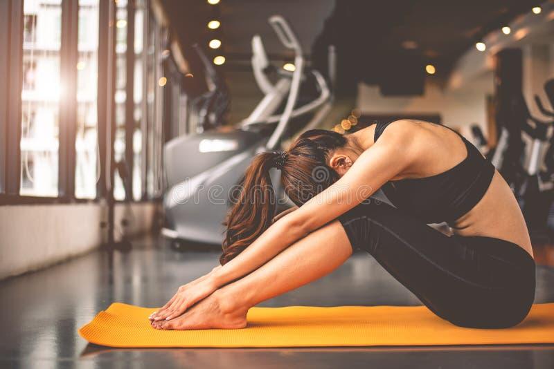 Frau, die verbiegendes Yoga tut und unten in den Eignungstrainings ausbilden Turnhallenmitte gegen?berstellt Lebensstilfrau, die  stockbild