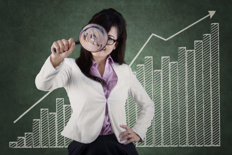 Frau, die Vergrößerungsglas verwendet, um Geschäftswachstum zu überwachen lizenzfreies stockbild
