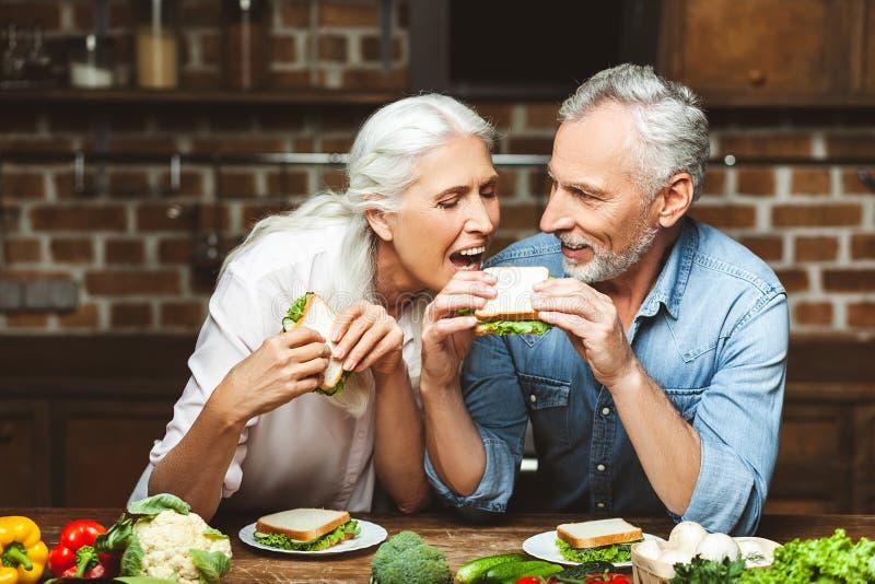 Frau, die versucht, Ehemannsandwich zu essen lizenzfreie stockfotografie