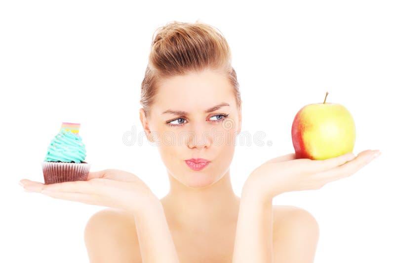 Frau, die versucht, eine Entscheidung zwischen kleinem Kuchen und Apfel zu treffen lizenzfreie stockfotos