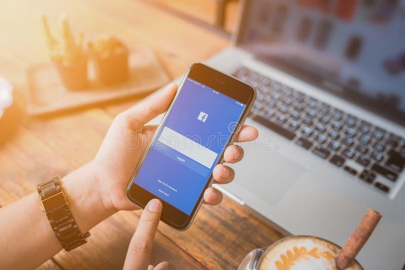 Frau, die versucht, Facebook-Anwendung unter Verwendung Apple-iPhone 6 anzumelden stockfoto